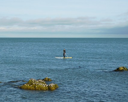 An image of a man stand-up paddle boarding.